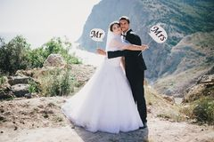 Bride and groom with Mr and Mrs signs. Just married beautiful young bride and groom standing with Mr and Mrs signs on the mountains background royalty free stock photos