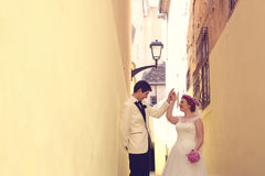 Bride and groom on a narrow street Royalty Free Stock Photos