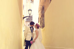 Bride and groom on a narrow street Stock Photo