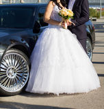 Bride and groom near car. Bride and groom standing in front of wedding car Stock Image