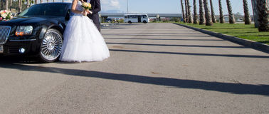 Bride and groom near car. Bride and groom standing in front of wedding car Royalty Free Stock Photos