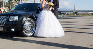 Bride and groom near car. Bride and groom standing in front of wedding car Royalty Free Stock Images