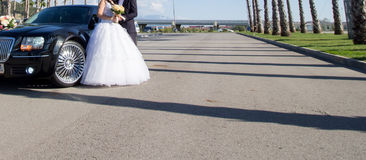 Bride and groom near car. Bride and groom standing in front of wedding car Stock Photography
