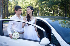 Bride and groom near the car, young happy couple Royalty Free Stock Image