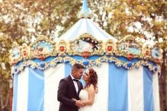 Bride and groom near carrousel Stock Photo