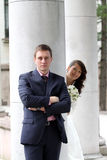 Bride and groom near columns in park Stock Image