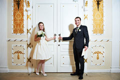 Bride and groom near doors of wedding hall Royalty Free Stock Photos