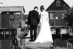 Bride and groom near houses on lake Stock Photos