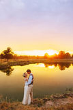 Bride and groom near the lake at sunset time Royalty Free Stock Photos
