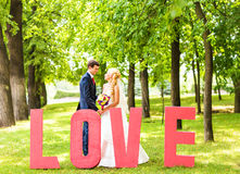 Bride and groom near the letter the word love, word love composed of letters Stock Photo