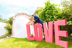 Bride and groom near the letter the word love, word love composed of letters Royalty Free Stock Photos