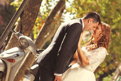 Bride and groom. Near a moped kissing Stock Photography
