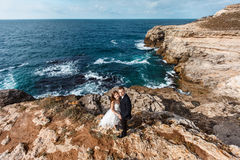 Bride and groom near the ocean. Hugging each other Stock Image