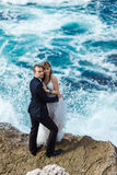 Bride and groom near the ocean. Hugging each other Stock Photo