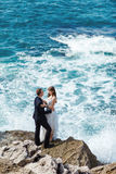 Bride and groom near the ocean. Hugging each other Royalty Free Stock Image