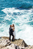 Bride and groom near the ocean. Hugging each other Stock Photos