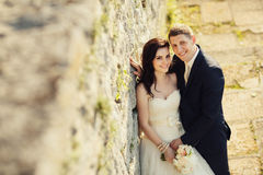 Bride and groom near old ruined castle wall Stock Images