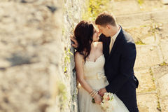Bride and groom near old ruined castle wall Royalty Free Stock Image