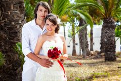 Bride and groom near palm-tree Stock Photography