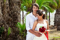 Bride and groom near palm-tree Royalty Free Stock Photo