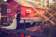 Bride and groom near red house Stock Photography