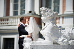 Bride and groom near sculpture of female lion Stock Photo