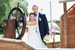 Bride and groom near ship steering wheel Royalty Free Stock Photos