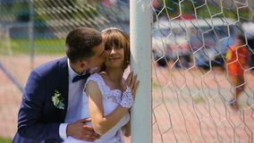 Bride and groom near soccer gate having fun time stock footage
