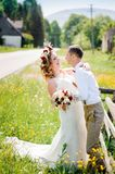 Bride and groom near to the road. Happy bride and groom standing near to the road and hugging Royalty Free Stock Photography