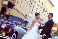 Bride and groom near vintage car Stock Image