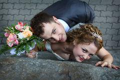 Bride and groom near a wall Royalty Free Stock Photos