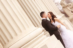 Bride and groom near white columns Stock Photos