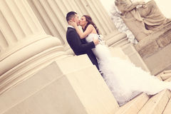 Bride and groom near white columns Stock Photo