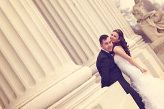 Bride and groom near white columns Stock Photography