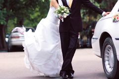 Bride and groom near white limousine, joyful stock images