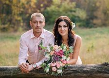 The bride and groom near the wooden fence. Portrait of a young couple close-up. People are laughing. The girl has a stock photos