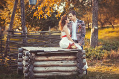 Bride and groom near the wooden well. In autumn park and looking at each other Royalty Free Stock Photos