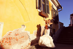 Bride and groom near yellow house Royalty Free Stock Image