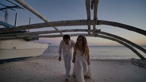 The bride and groom, newlyweds, walk at sunset on a tropical beach by the ocean. They are posing against the backdrop of. An old Philippine boat stock footage
