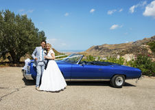 Bride and Groom next to wedding car Stock Images