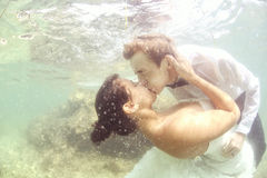 Bride and groom in the ocean water diving Stock Photo