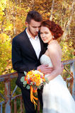 Bride and groom at the old bridge. Autumn outdoor setting. Stock Photos