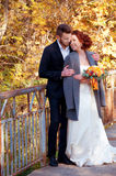 Bride and groom at the old bridge. Autumn outdoor setting. Royalty Free Stock Image