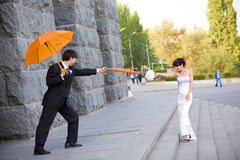 Bride and groom with orange umbrellas Stock Photo