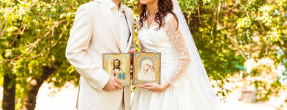 Bride and groom after orthodox wedding ceremony. Wedding couple with icons royalty free stock photography