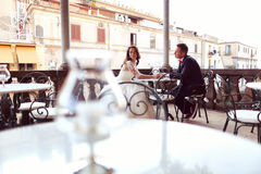 Bride and groom in a outdoor restaurant Stock Images