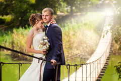 Bride and groom outdoors on bridge Royalty Free Stock Image