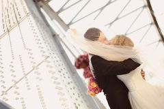 Bride and groom outdoors kissing on their wedding day Stock Photo
