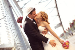 Bride and groom outdoors kissing on their wedding day Royalty Free Stock Images