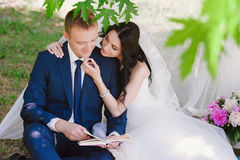 Bride and groom outdoors smiling cuddling and reading books, decor, peonies, flowers, lifestyle, marriage, family, love Royalty Free Stock Photo
